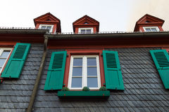 European windows with green wooden shutters in old house. Outdoo Stock Photo
