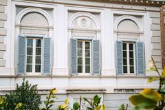 European windows with wooden shutters. Old house exterior. Rome, Italy Royalty Free Stock Images