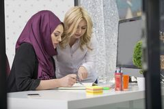 European woman and asian muslim woman working together on same project stock photography