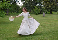 European woman dancing and touching her hat in vintage dress in park. Royalty Free Stock Images