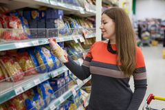 Woman read package of food while making a choice in grocery warehouse. European woman read package of food while making a choice in grocery warehouse stock images