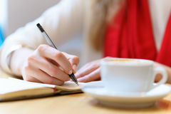 European woman with red scarf is writing by pen somthing in the notepad near white cup of coffee on table. At day time Stock Photo
