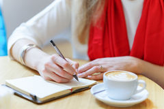 European woman with red scarf is writing by pen somthing in the notepad near white cup of coffee on table Stock Photography