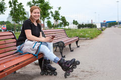 European woman on roller skates sits on bench with a modile phone in her hands Stock Photo