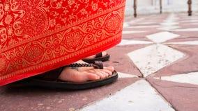 European Woman`s foot and orange red floral Sari Stock Photos