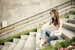 European woman sitting on steps Royalty Free Stock Photos