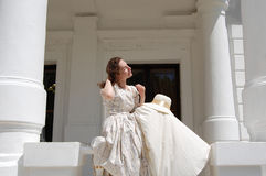 European woman sitting in sunshine and touching hair in vintage dress near palace. Stock Photography
