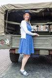European woman standing against military jeep stock photo