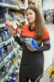 European woman thinking while making choice between two package with food in grocery warehouse Royalty Free Stock Photography