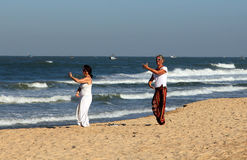 European women are engaged in a dynamic yoga on Candolim beach Stock Photo