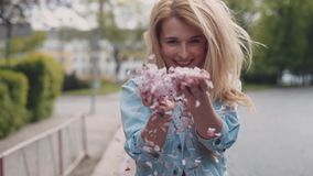 European young blonde attractive girl is moving down the park, then she turns and throws the petals of cherries blossom stock video