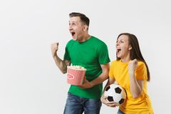 European young couple, woman, man, football fans in yellow green t-shirt cheer up support team with soccer ball bucket. Of popcorn isolated on white background stock photo