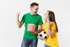 European young couple, woman, man, football fans in yellow green t-shirt cheer up support team with soccer ball bucket. Of popcorn isolated on white background royalty free stock photography