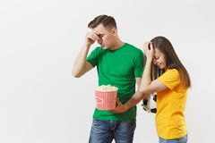 European upset couple, woman, man, football fans in yellow green t-shirt cheer up support team with soccer ball bucket. European young couple, woman, man stock photography