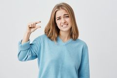 European young female wearing blue sweater with blonde hair showing something small in size with hands, gesturing. European young female wearing blue sweater stock photos