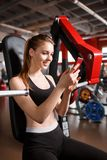 A girl is clapping a mobile phone while sitting in the gym on a simulator. Stock Photos