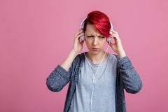 A girl with ear-phones, is grimaces her face from displeasure. A European young girl with red hair and ear-phones on her neck stands and grimaces her face from Royalty Free Stock Photos