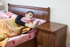 European young man sleeping the day away, looking at time in bed Royalty Free Stock Photography