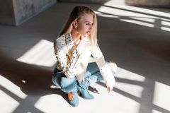 European young woman model in vintage leather jacket in blue trendy ripped jeans in green fashionable cowboy boots posing sitting. Indoors with sunlight royalty free stock image