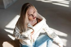 European young woman in vintage leather jacket in fashionable ripped jeans in blue trendy cowboy boots posing sitting indoors. With sunlight. Beautiful sensual stock photography