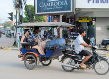 Europeans with cambodian tuk tuk driver on the street of asian city Royalty Free Stock Image