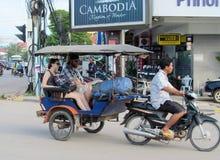 Europeans with cambodian tuk tuk driver on the street of asian city. Europeans with cambodian rickshaw tuk tuk driver on the street of asian city. Riksha Royalty Free Stock Image