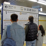 Europeans in the Japanese subway. Two European men and a girl at a loss in the Japanese metro plan Stock Photos