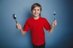 Europees-kijkend jongen van tien jaar die een lepel houden Stock Foto