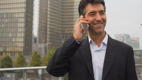 Europeisk affärsman som går och talar vid telefonen stock video