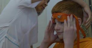 Europeisk barnuppförandeelectroencephalography Ett processfragment Rheoencephalography - en doktor fäster på elektroder stock video