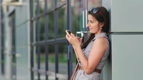 Europeisk flicka i aftonmetropolisen genom att använda smartphonen för kommunikation eller att prata arkivfilmer