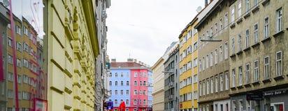 Europeisk gata fodrad både sidor med byggnader och rosa och blått arkivfoto