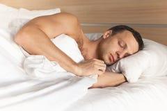 Europeisk man för stående som sover i vit säng royaltyfri foto
