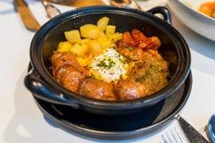 Europeisk mat: Bakat ägg med korven, den körsbärsröda tomaten och potatisen Arkivfoto