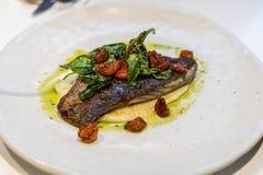 Europeisk mat: Panna-stekt havsbraxen med körsbärsröda tomater och basilika Royaltyfria Bilder