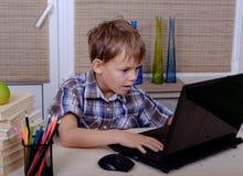 Europeisk pojke på tabellen med böcker och bärbara datorn Royaltyfria Bilder