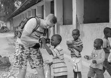 Europeisk turist- visningkamera till afrikanska barn Royaltyfri Foto