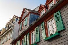 Europeiska fönster med gröna träslutare i gammalt hus Outdoo Royaltyfria Bilder