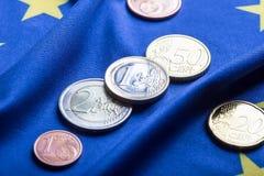 Europeiska flagga- och europengar Mynt och europeisk valuta för sedlar som läggas fritt på Euren Arkivbild