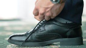 Europeiska manhänder för närbild i armbandsuret som binder skosnöret på den formella eller festliga klassikersvartskon arkivfilmer