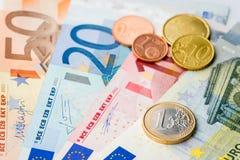 Europeiska pengar - ett euromynt med eurocent och sedlar Arkivbilder