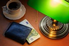 Europeiska pengar, på ett stilfullt skrivbord som tänds med en packa ihop lampa arkivbild