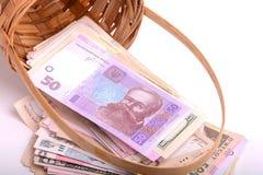Europeiska pengar på träkorgen, hryvnia, dollar, euro Arkivbild