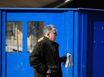 Europeiska pensionärer - gamal man med en tidning som går på stren Arkivbilder