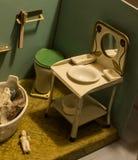 Europeiska tappningleksaker - dockamöblemang för badrummet och två porslindockor 1/12 royaltyfria bilder