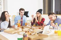 Europeiskt folk som äter på arbetsplatsen arkivbild