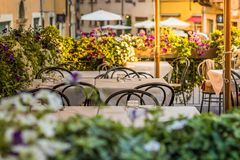 Europeiskt gatarestaurang eller kafé Tabeller med vita borddukar utomhus royaltyfria bilder