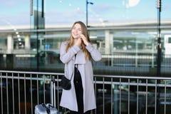 Europeiskt kvinnaanseende med valise och samtal vid smartpone nära flygplats arkivbild
