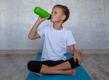 Europeiskt pojkedricksvatten från en flaska på den matta idrottshallen royaltyfria bilder