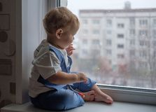 Europeiskt pojkesammanträde på fönsterbrädan och se ut fönstret royaltyfria bilder